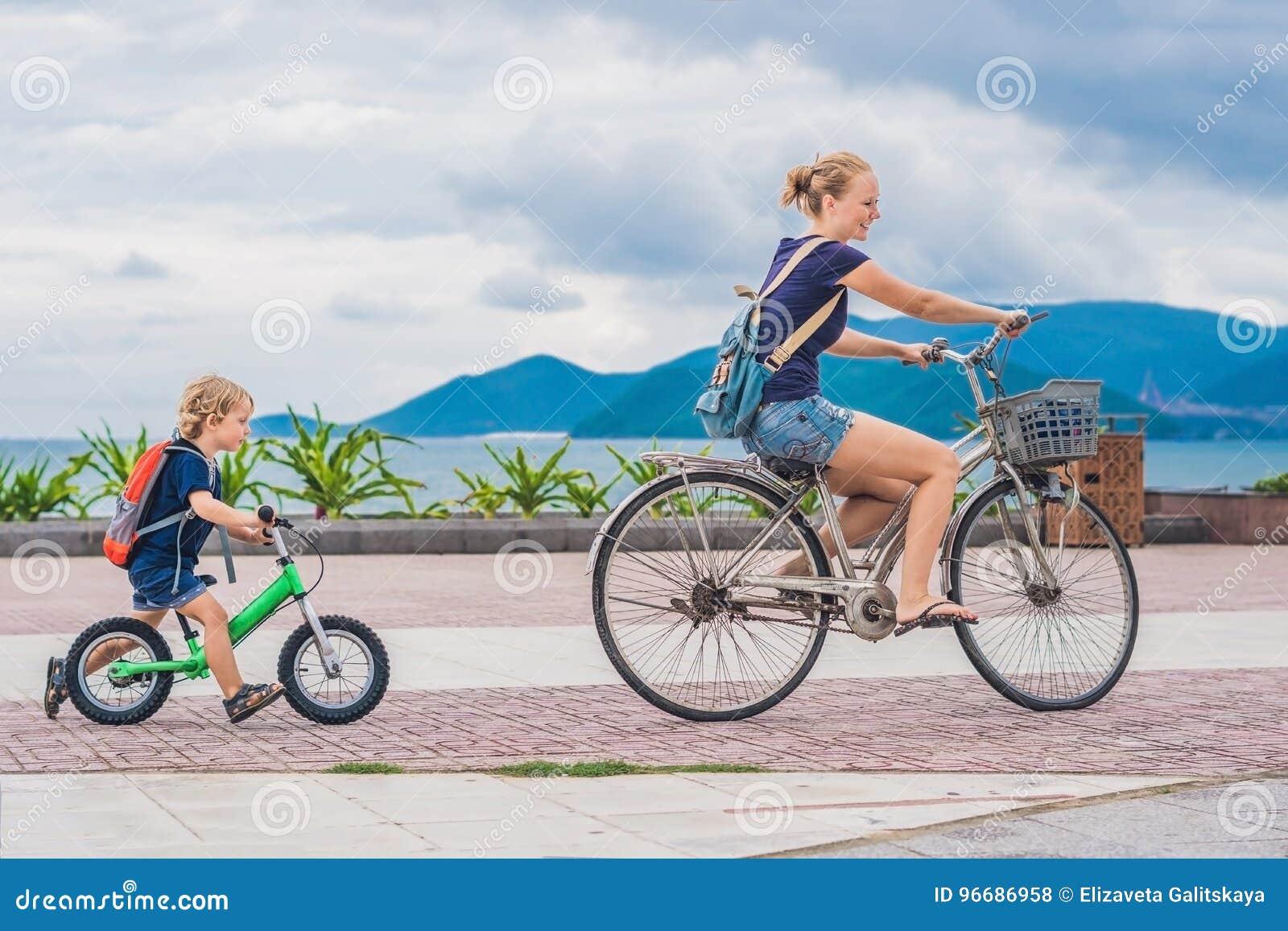 La familia feliz está montando las bicis al aire libre y la sonrisa Mamá en una bici