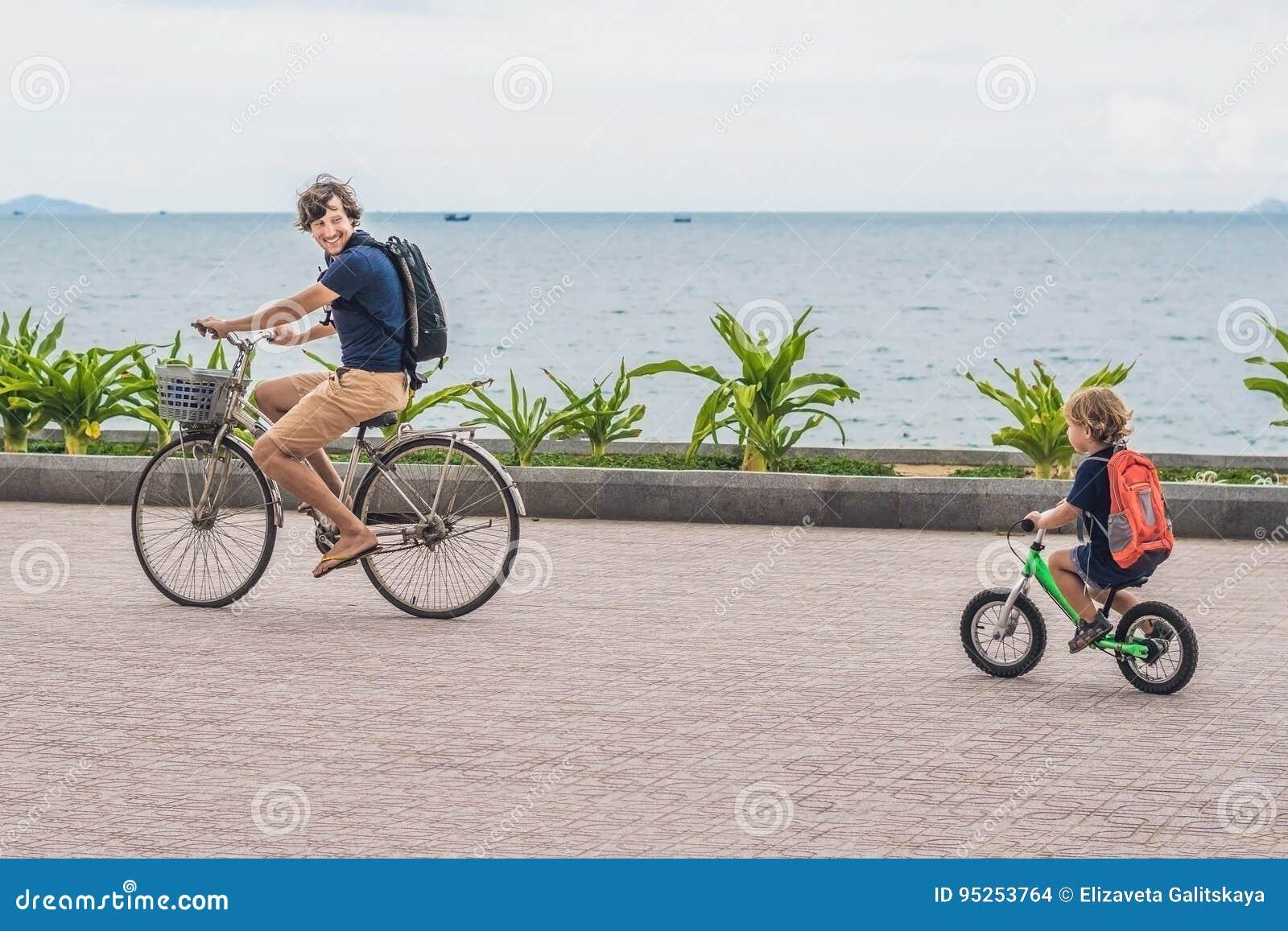 La familia feliz está montando las bicis al aire libre y la sonrisa Padre en un b