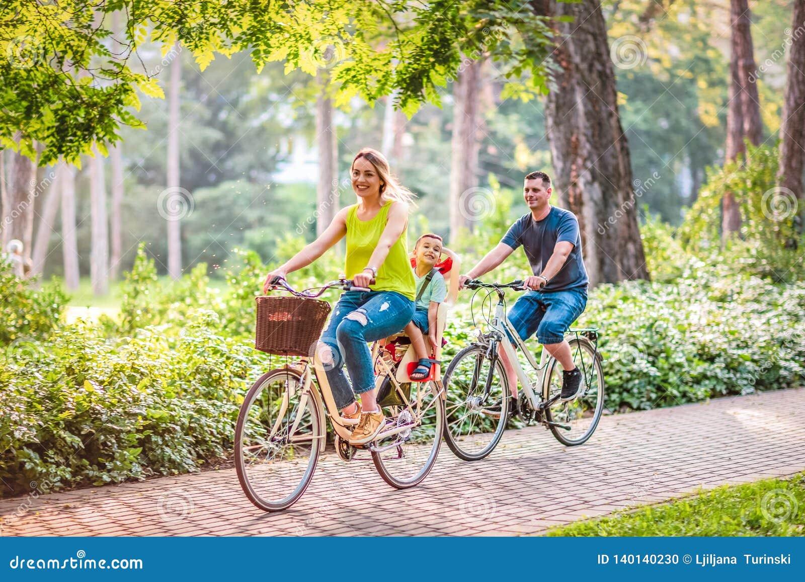 La familia feliz está montando las bicis al aire libre
