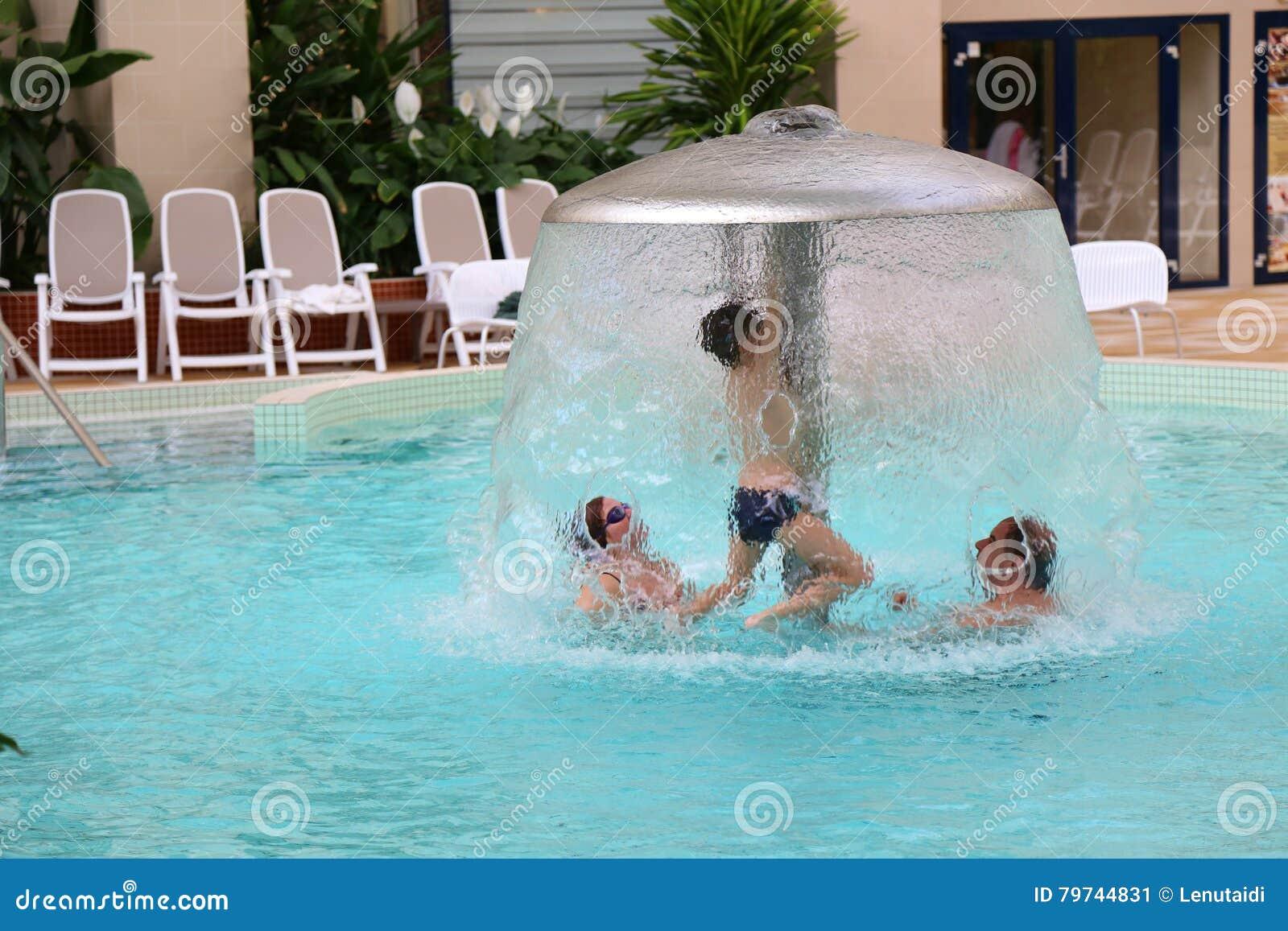 La familia goza junta en piscina termal