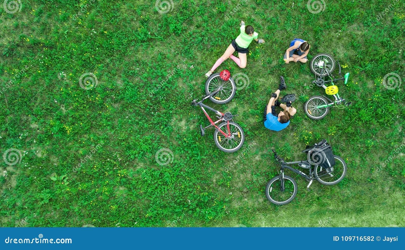 La familia que completa un ciclo en la opinión aérea de las bicis al aire libre desde arriba, los padres activos con el niño se d