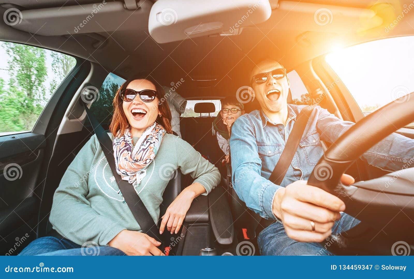 La familia tradicional joven alegre tiene un viaje auto largo y canto en voz alta de la canción preferida junta Concepto del coch