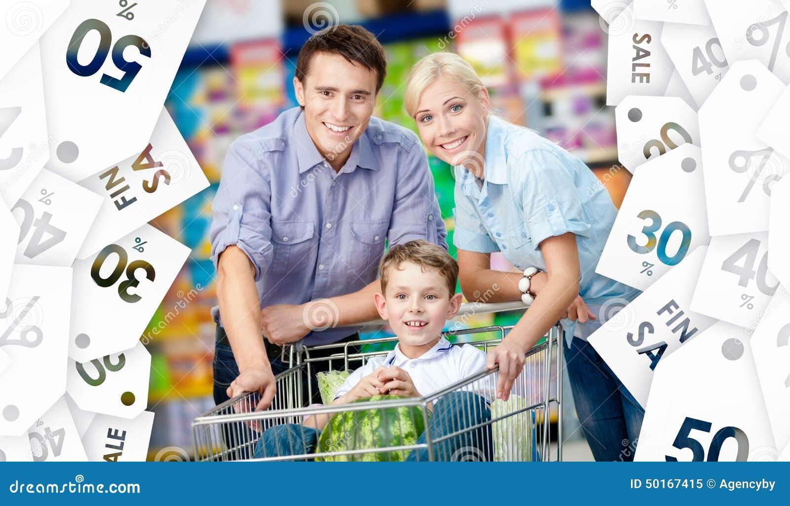 La famille conduit le chariot à achats avec la nourriture