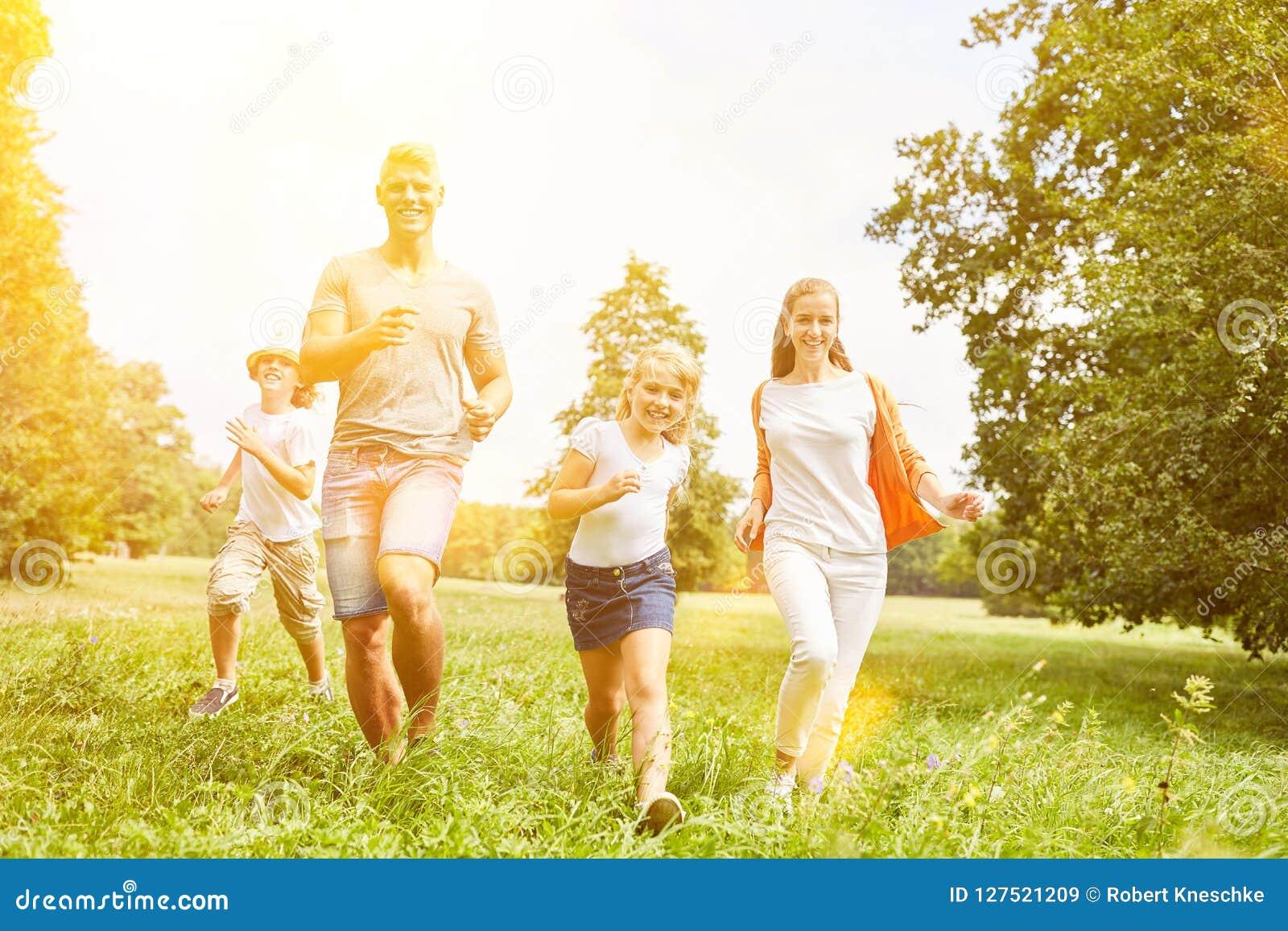 La famille et les enfants heureux courent ensemble comme sport