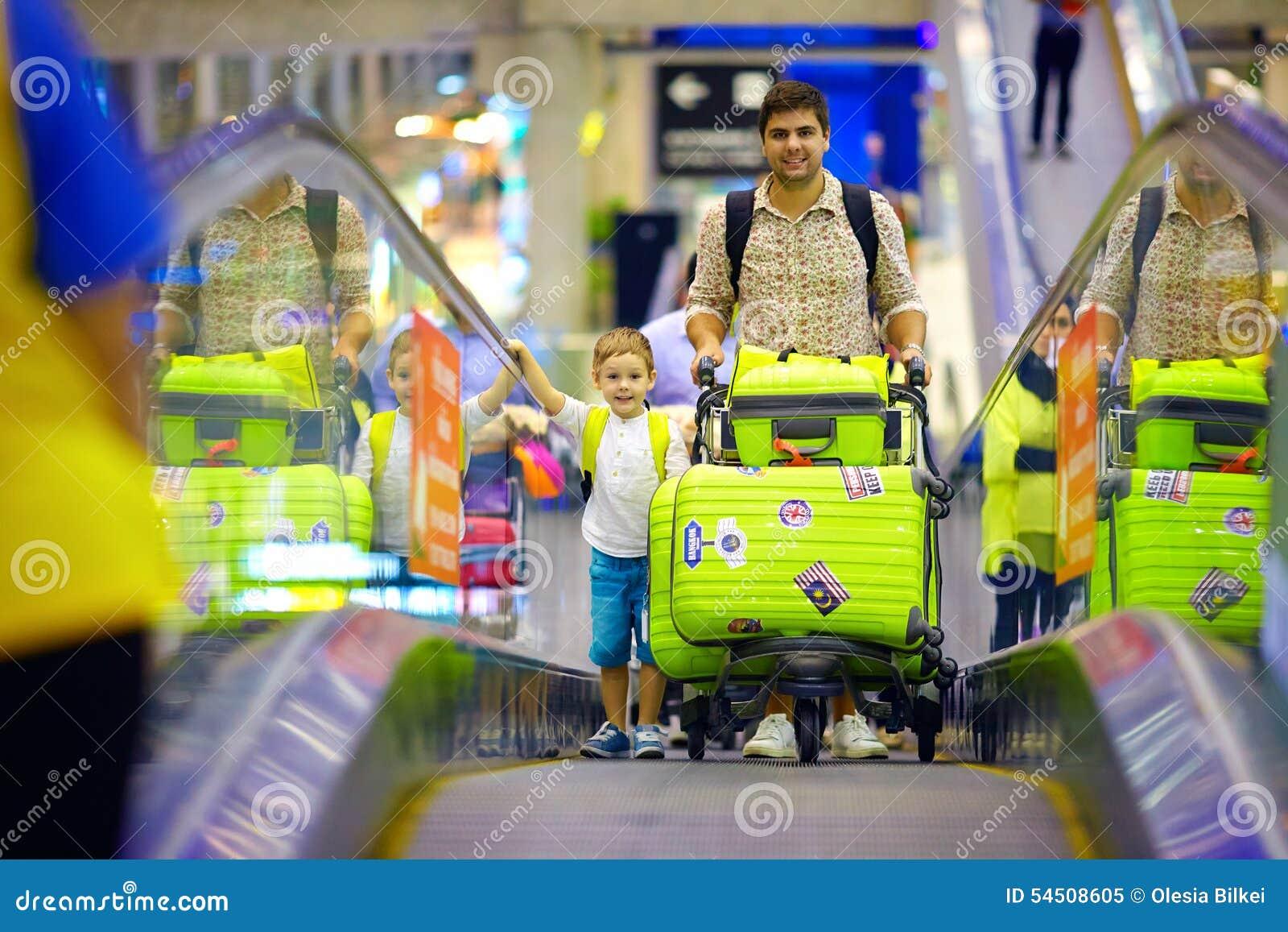 La famille heureuse avec des bagages sur le convoyeur dans l aéroport, préparent pour voyager