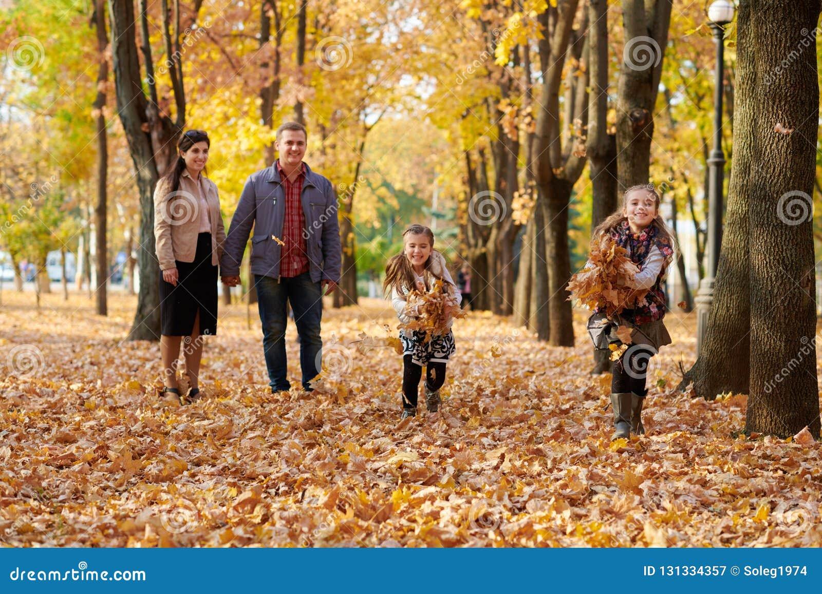 La famille heureuse est en parc de ville d automne Enfants et parents courant avec des feuilles Ils posant, souriant, jouant et a