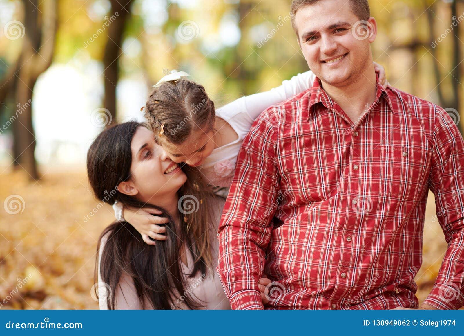 La famille heureuse est en parc de ville d automne Enfants et parents Ils posant, souriant, jouant et ayant l amusement Arbres ja