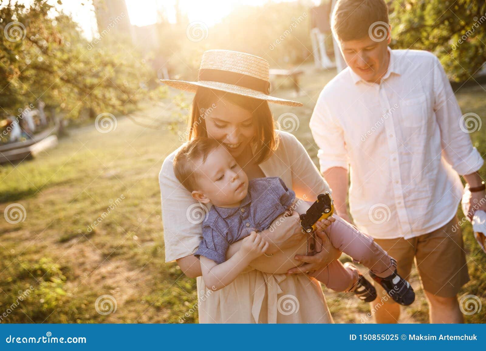 La famille heureuse marche le togther dans le jardin La mère joue avec son fils et s inquiète le sur des mains Elle sourit