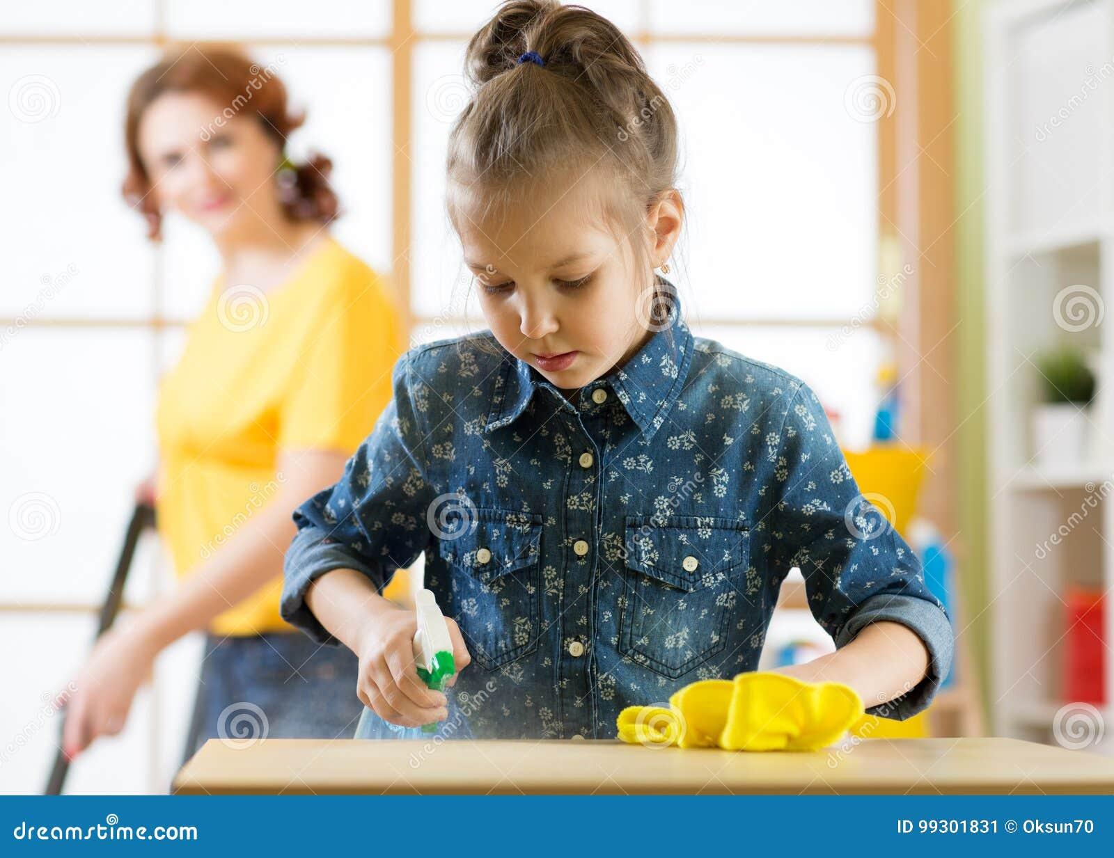 La famille heureuse nettoie la pièce La mère et sa fille d enfant font le nettoyage dans la maison La femme et peu de fille d enf