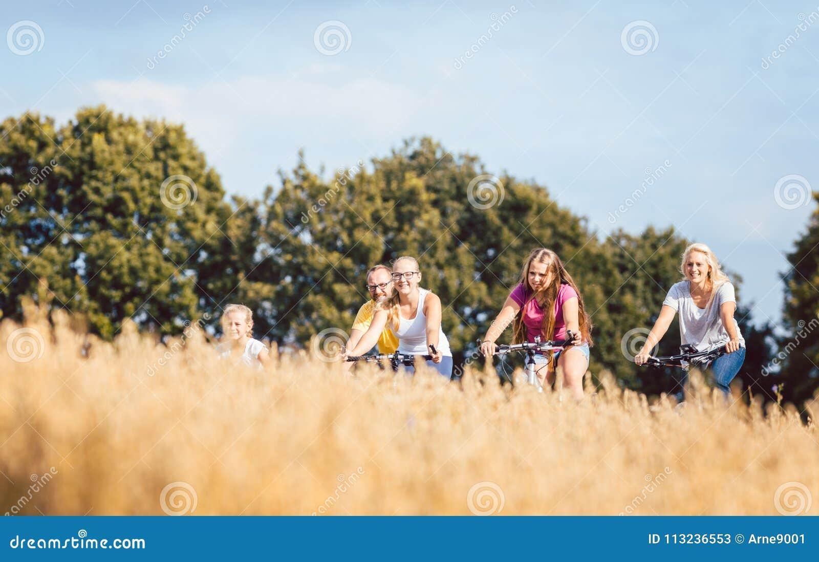 La famille montant leurs vélos a tiré au-dessus d un champ de grain