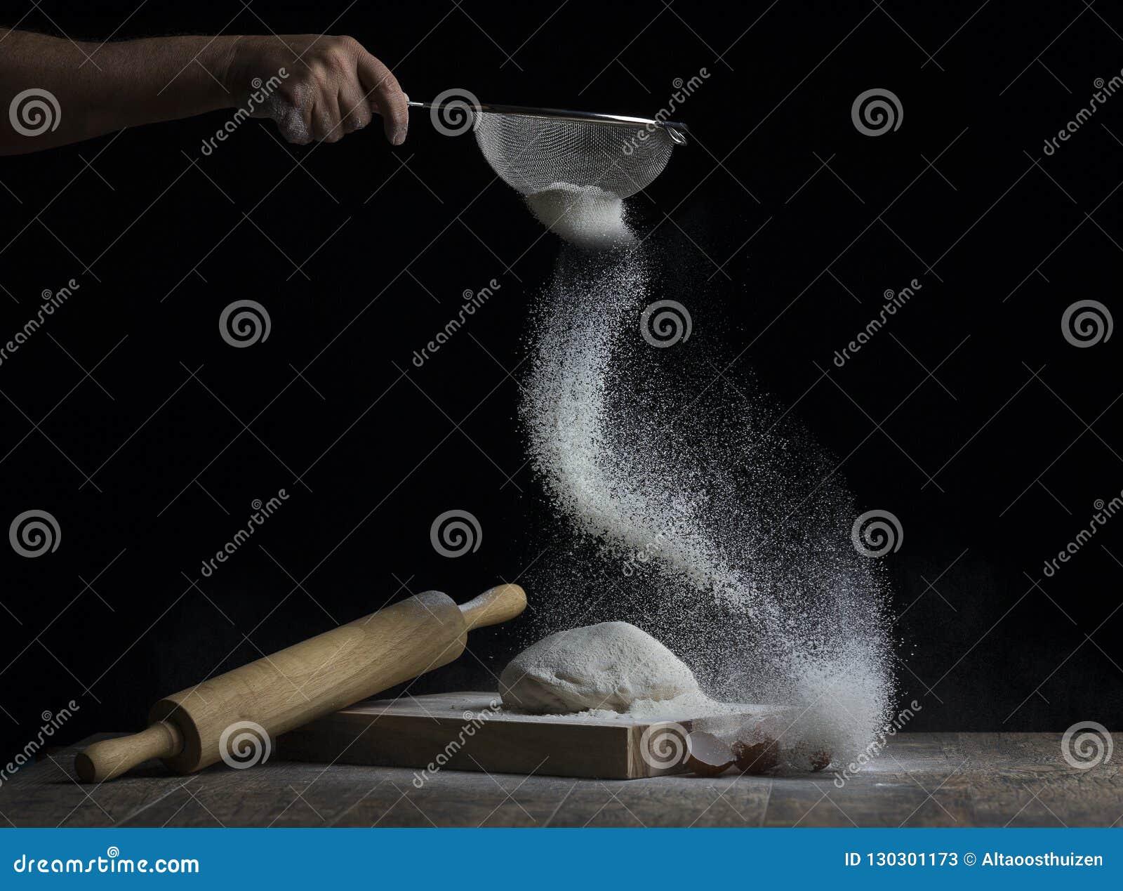 La farina è spruzzata sopra una palla di pasta su un bordo di legno con la r
