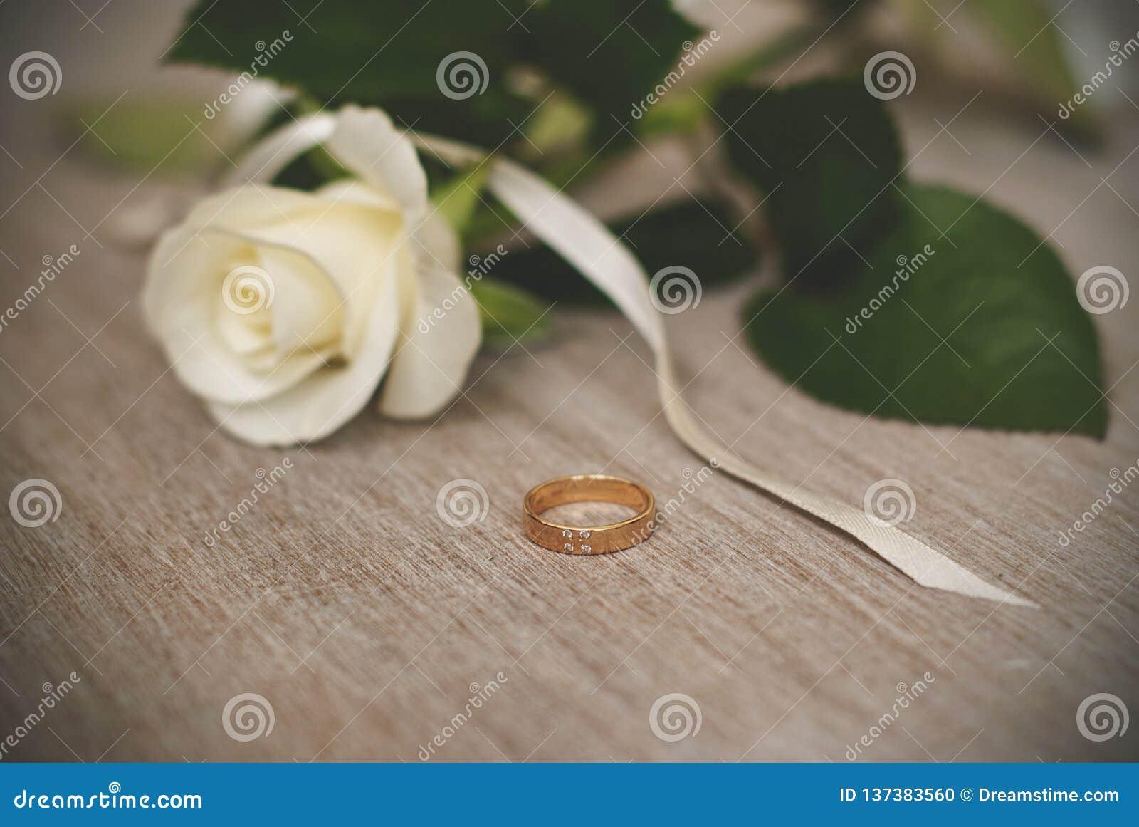 La fede nuziale e la crema sono aumentato Simboli di nozze, attributi Festa, celebrazione Macro sfuocatura