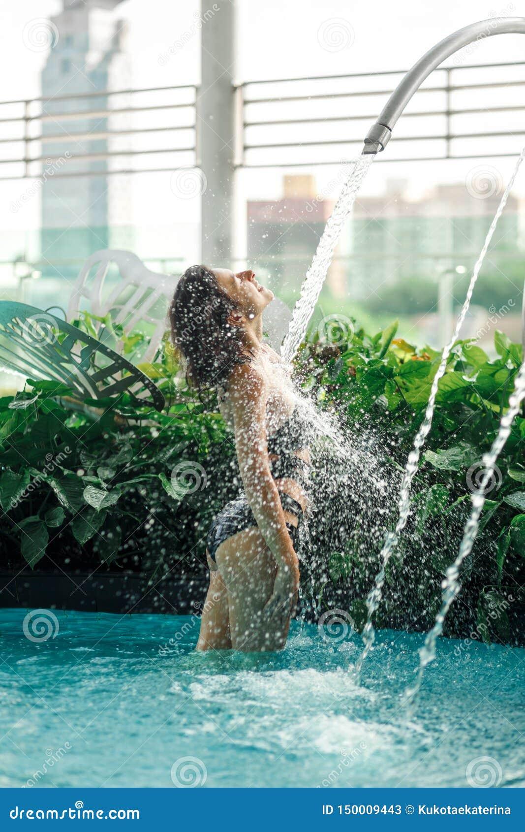 La femelle mince sexy dans le maillot de bain prend la douche dans la piscine entre les buissons verts sur le dessus de toit avec