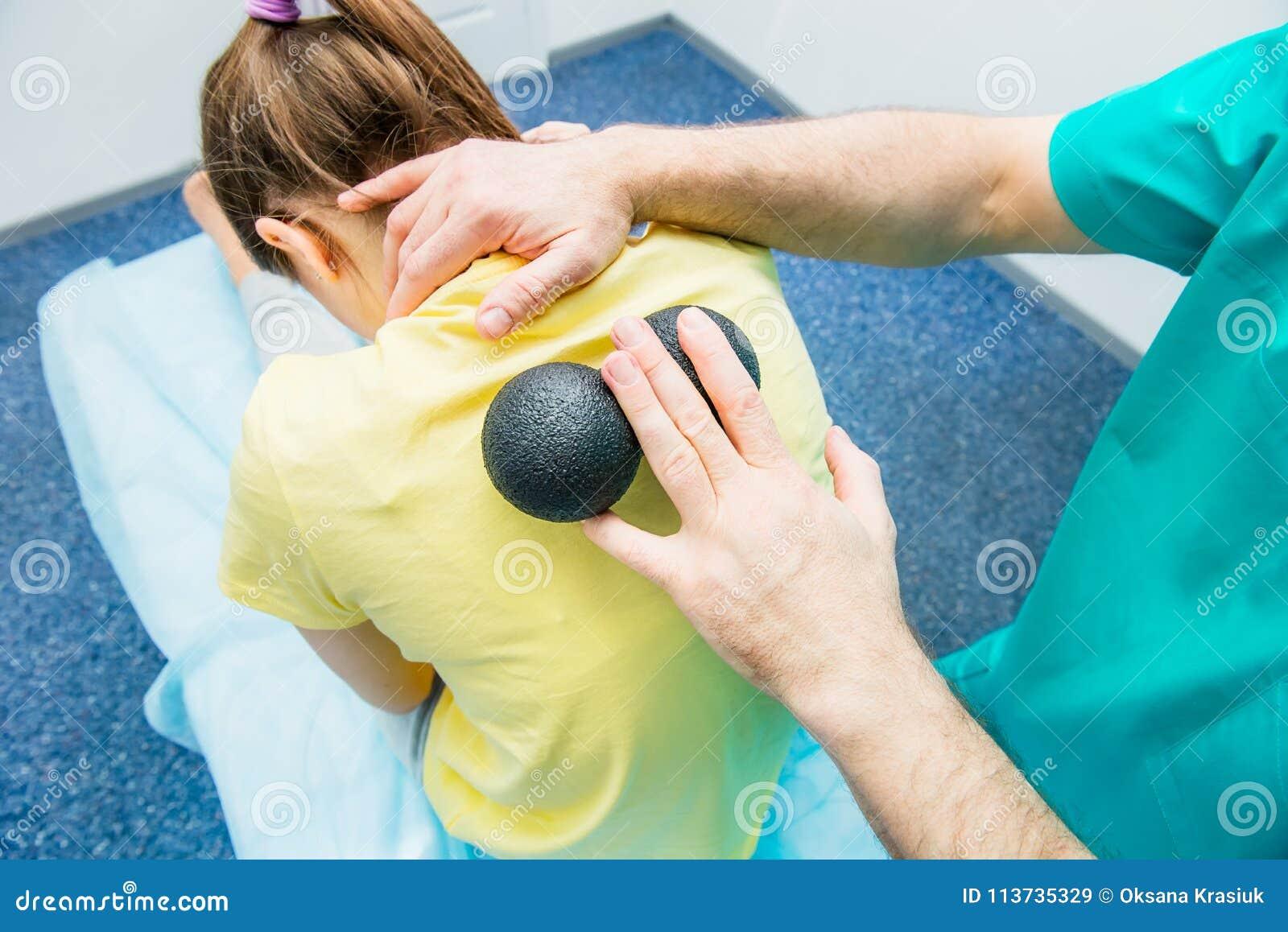 La femme à la physiothérapie recevant le massage de boule du chiroprakteur du thérapeute A traite l épine thoracique patiente du