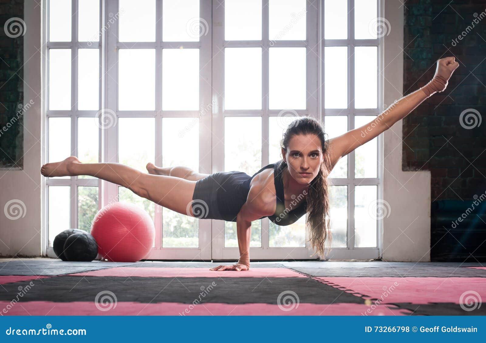La femme équilibrant tout en faisant une une main poussent montrer la puissance