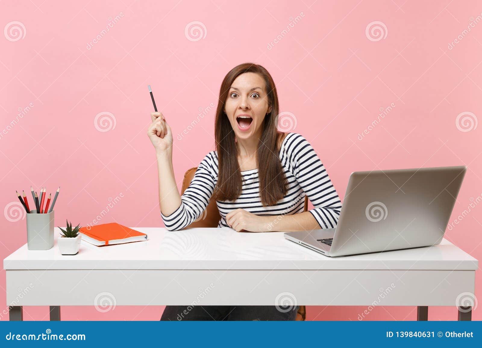La femme étonnée Shocked dirigeant le crayon s asseyent et travaillent au bureau blanc avec l ordinateur portable contemporain de