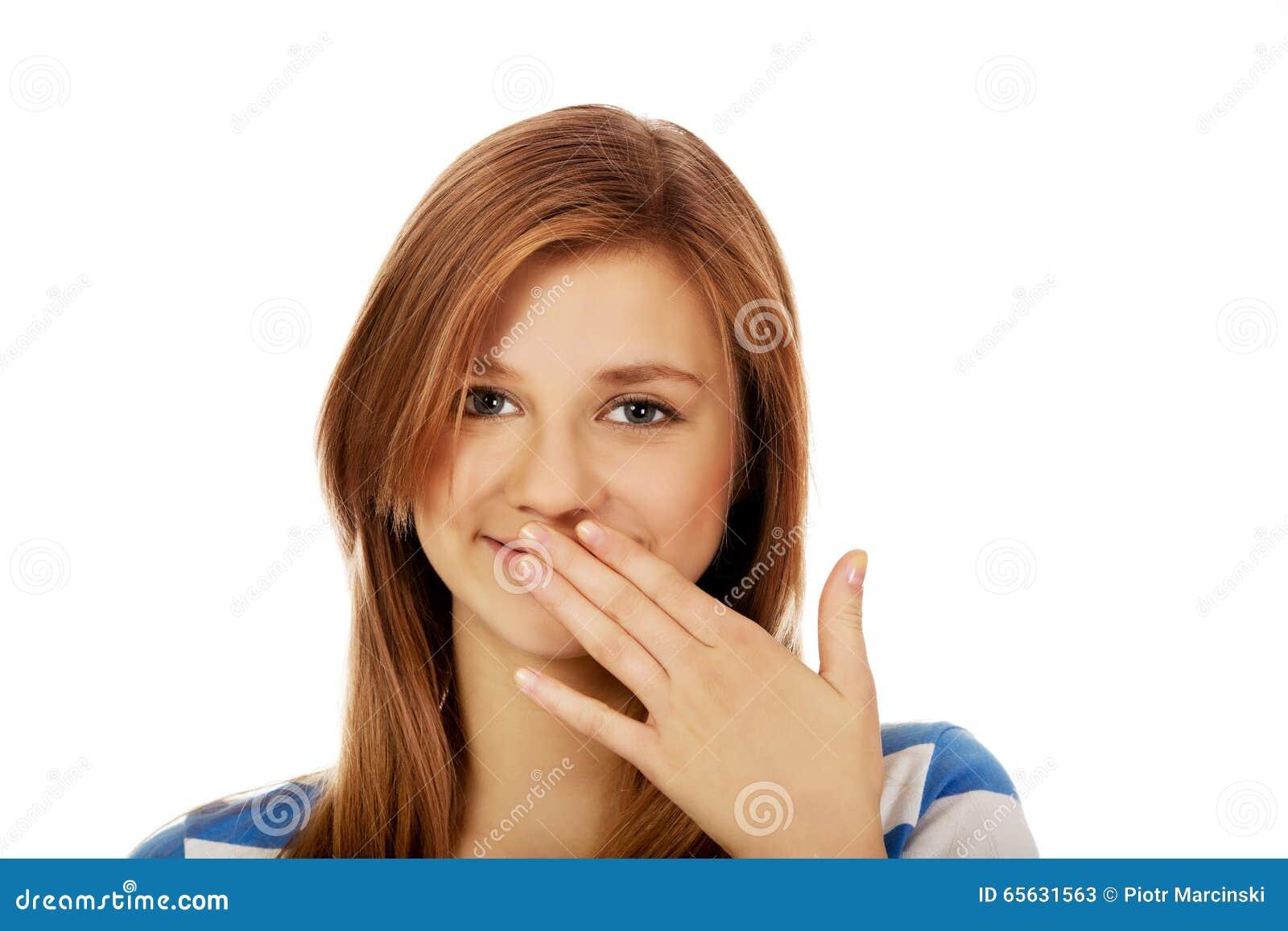 La femme adolescente rit nerveusement couvrant sa bouche de main