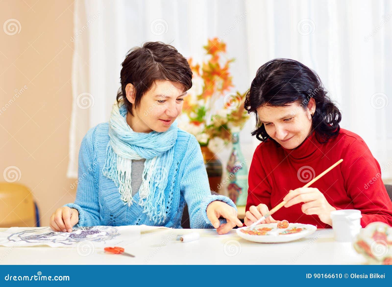 La femme adulte avec les besoins spéciaux sont engagées dedans handcraft au centre de réhabilitation