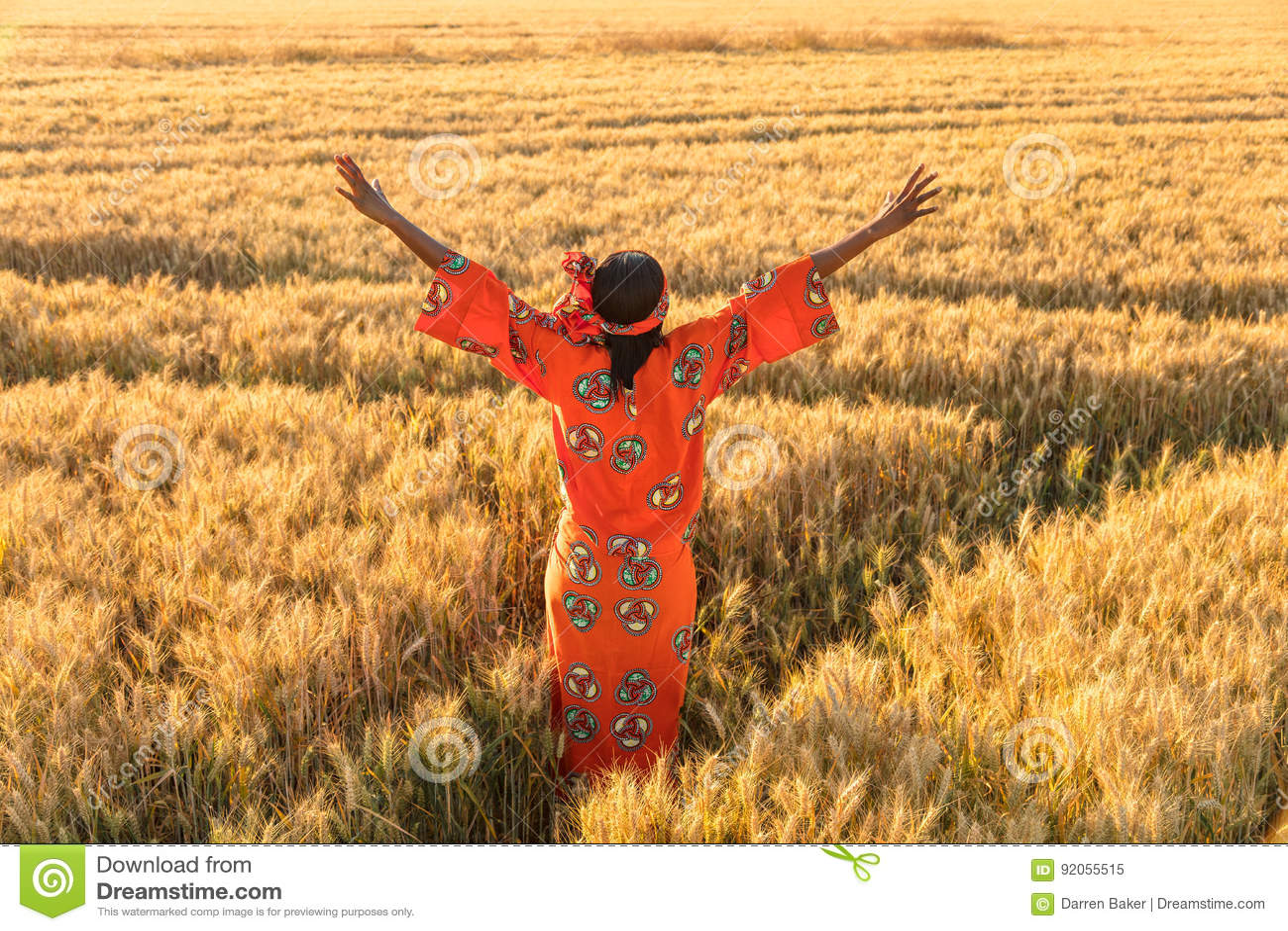 La femme africaine dans des bras traditionnels de vêtements a augmenté dans le domaine de l hôte
