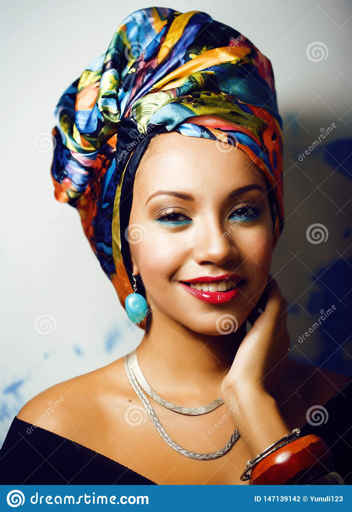 La femme africaine intelligente de beaut? avec cr?atif composent, ch?le sur la t?te comme le sourire cubian de plan rapproch?