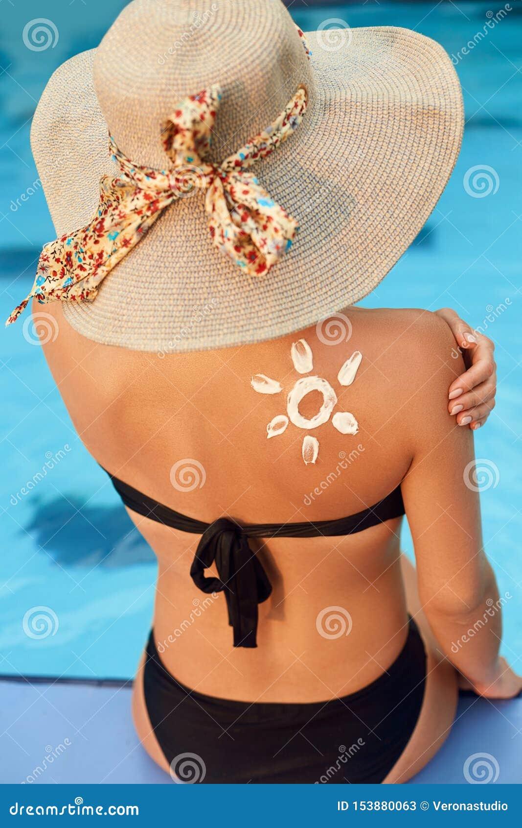 La femme appliquent la protection de crème du soleil sur l épaule bronzée Soin vieillissant de corps de protection du soleil de s