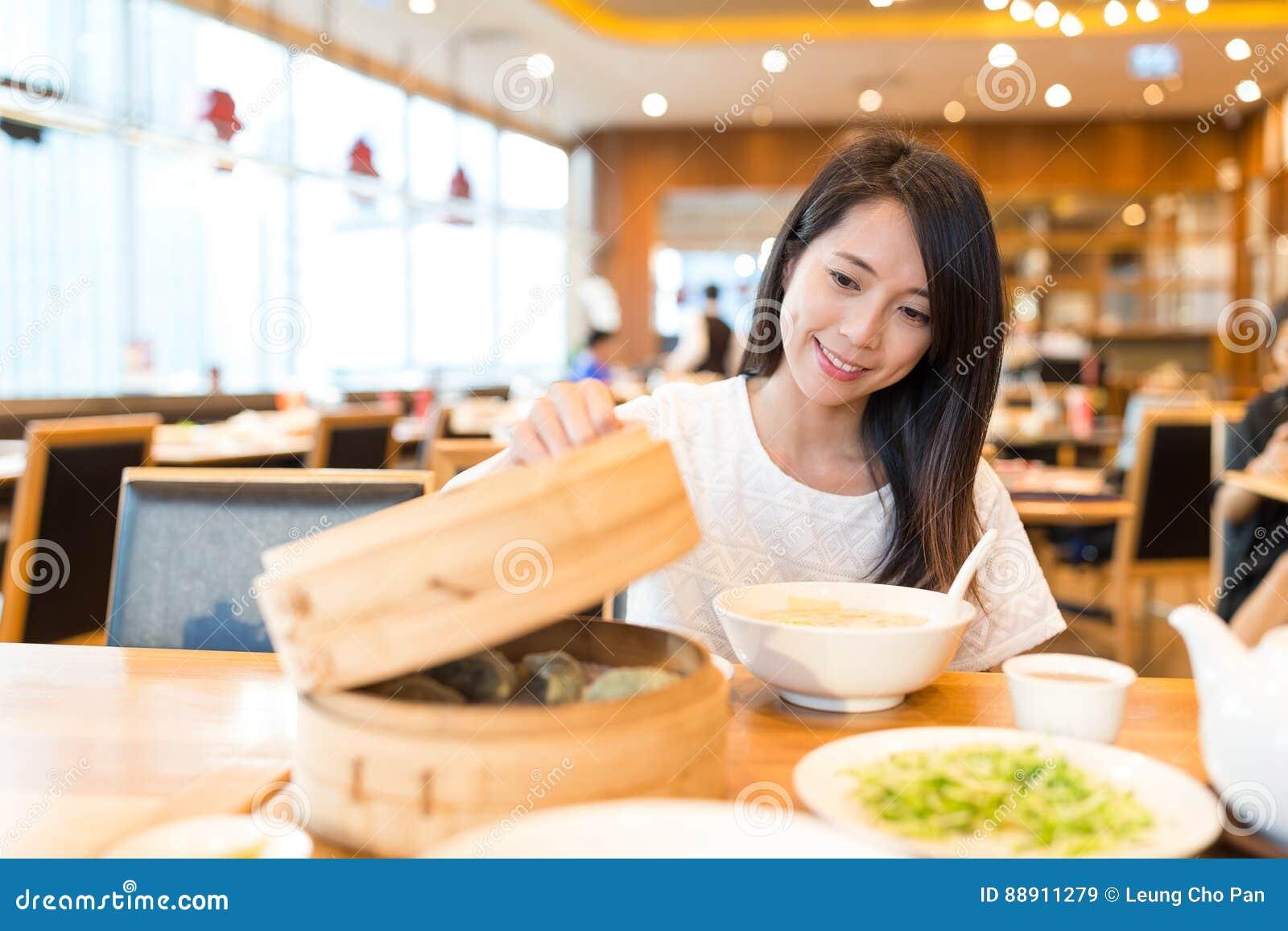 La femme apprécient le repas dans le restaurant chinois