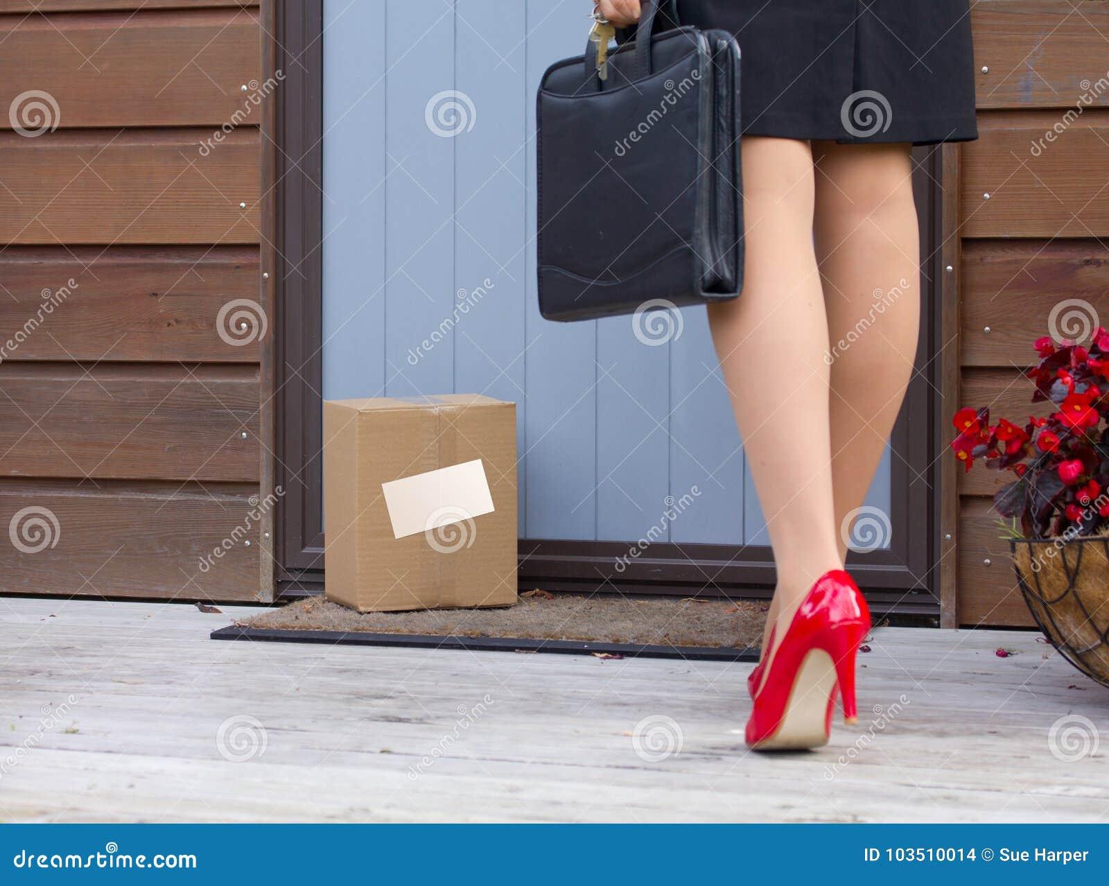 La femme arrive à la maison après travail pour libérer le colis de la livraison à la porte