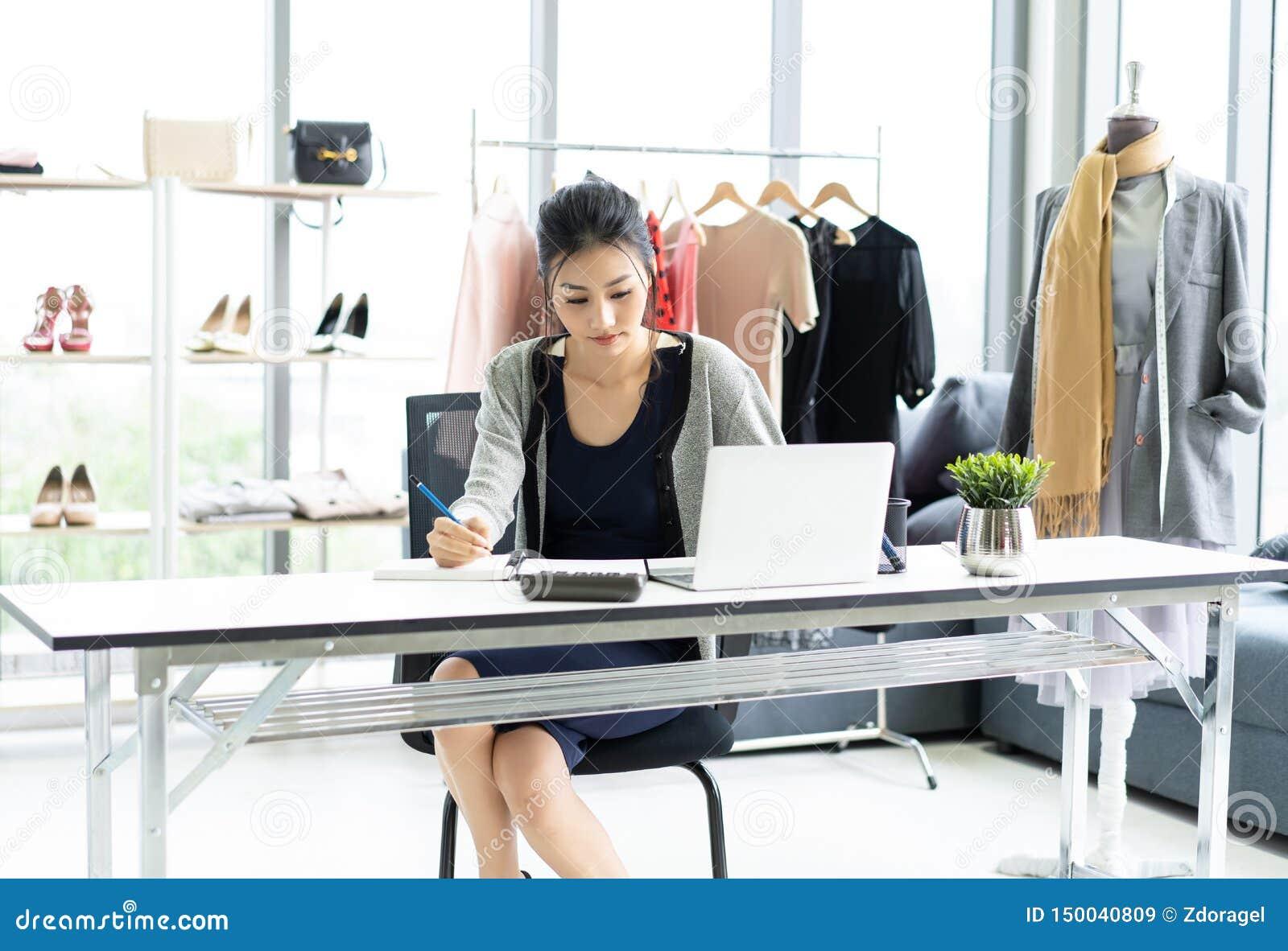 La femme asiatique de jeunes affaires s asseyant à la table et prenant des notes dans le carnet sur la table est ordinateur porta