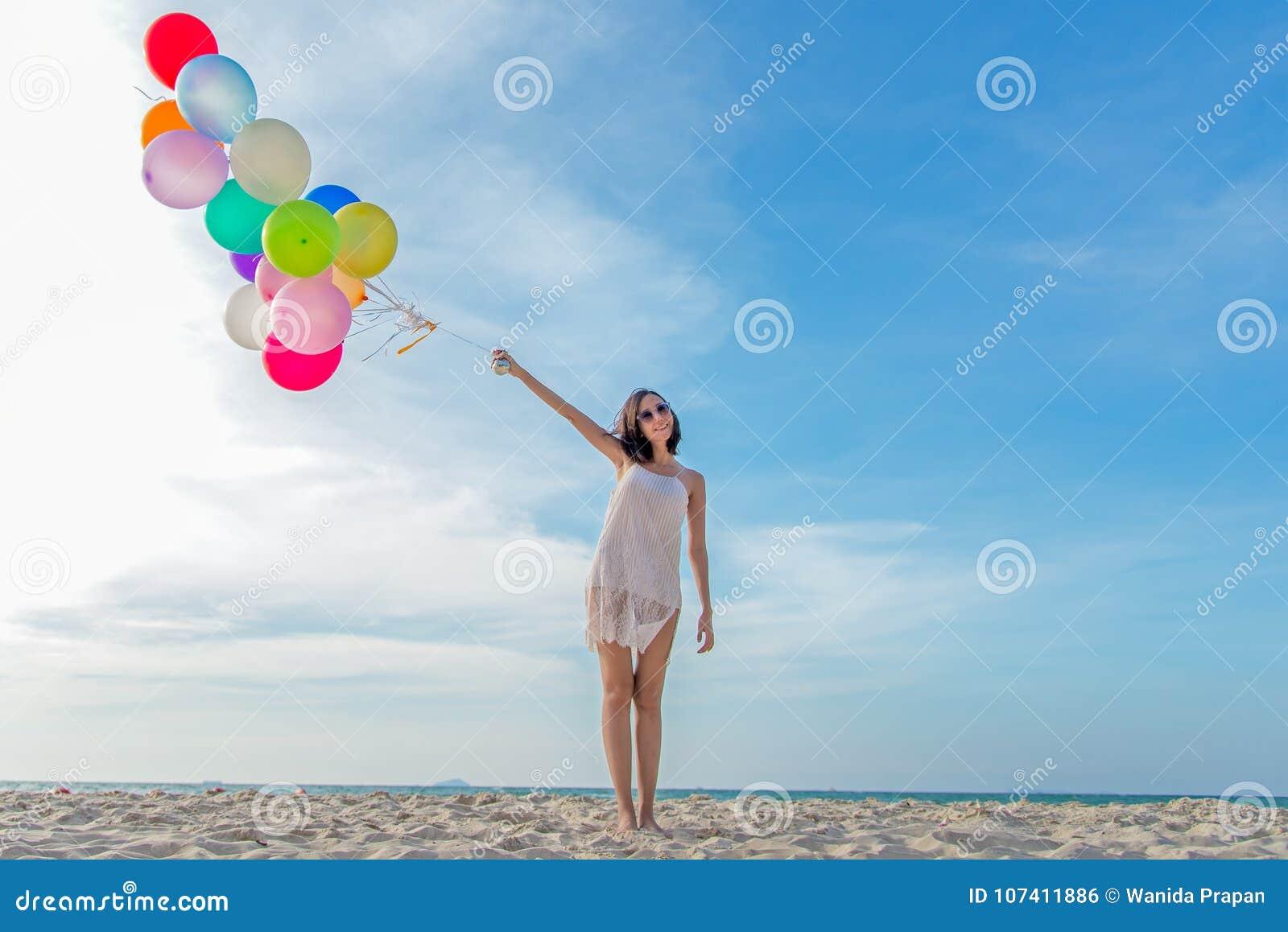 La femme asiatique de sourire de mode de vie remettent tenir le ballon sur la plage Détendez et appréciez dans des vacances d été