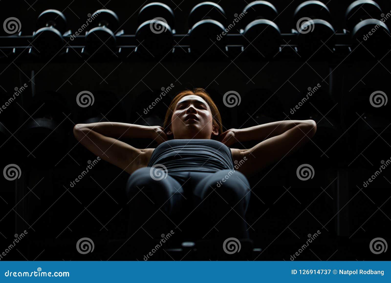 La femme asiatique de sport que faire se reposent se lève sur l étagère d haltères dans le St de forme physique