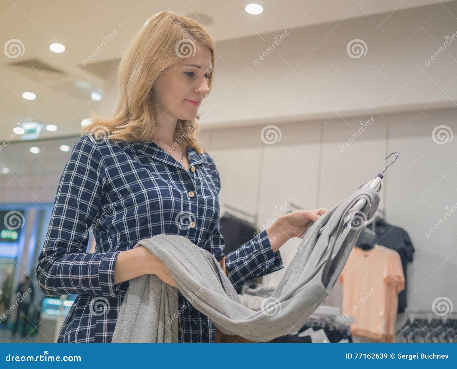 La femme attirante choisit des vêtements dans une boutique Le concept du shopp