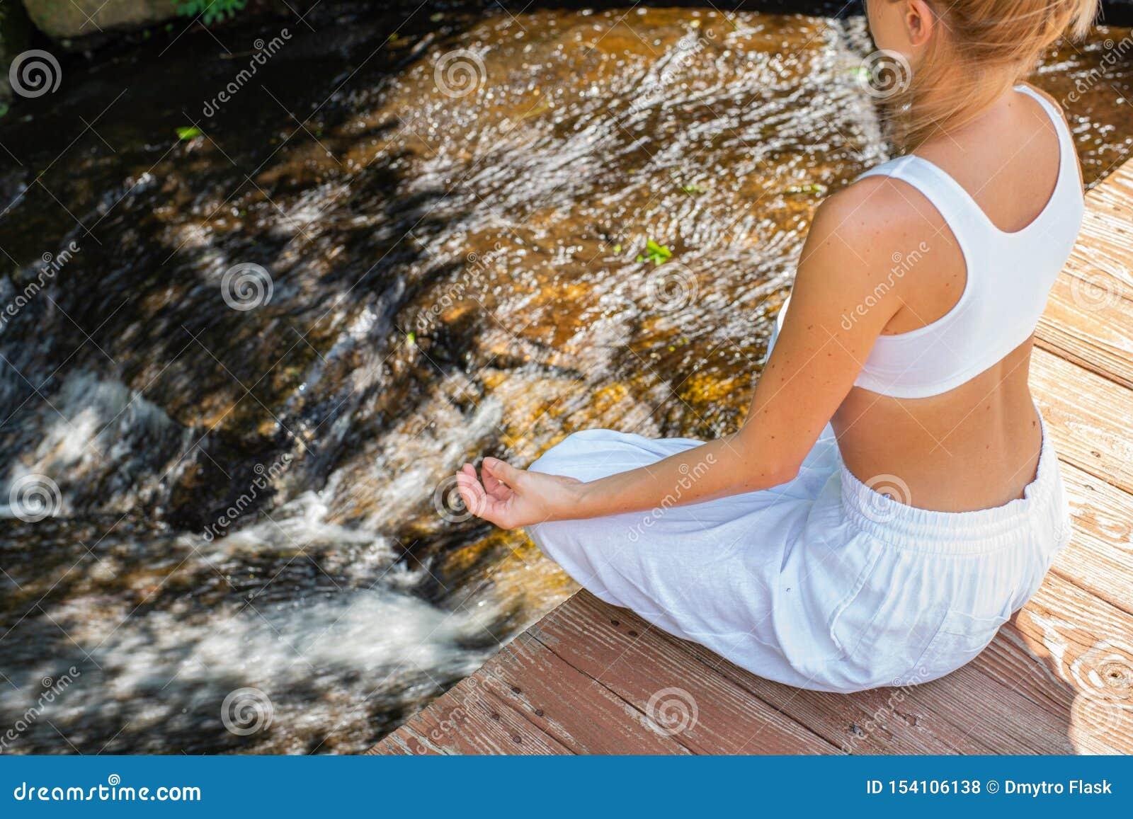 La femme attirante pratique le yoga et la méditation, se reposant dans la pose de lotus près de la cascade dans le matin
