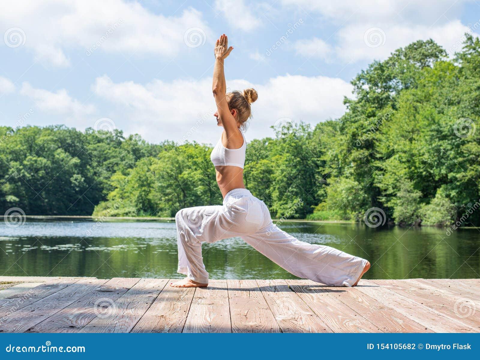 La femme attirante pratique le yoga, faisant la pose de Virabhadrasana I, se tenant dans la pose de guerrier près du lac