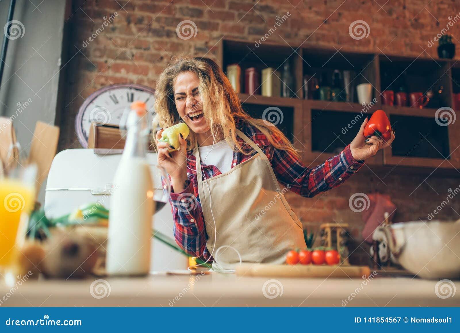 La femme au foyer dans un tablier joue avec le poivre frais