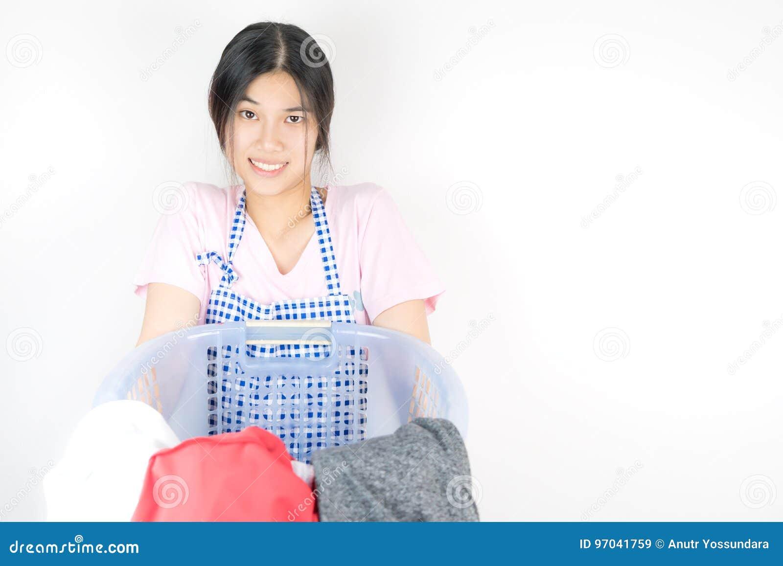 La femme au foyer drôle porte un panier complètement de blanchisserie
