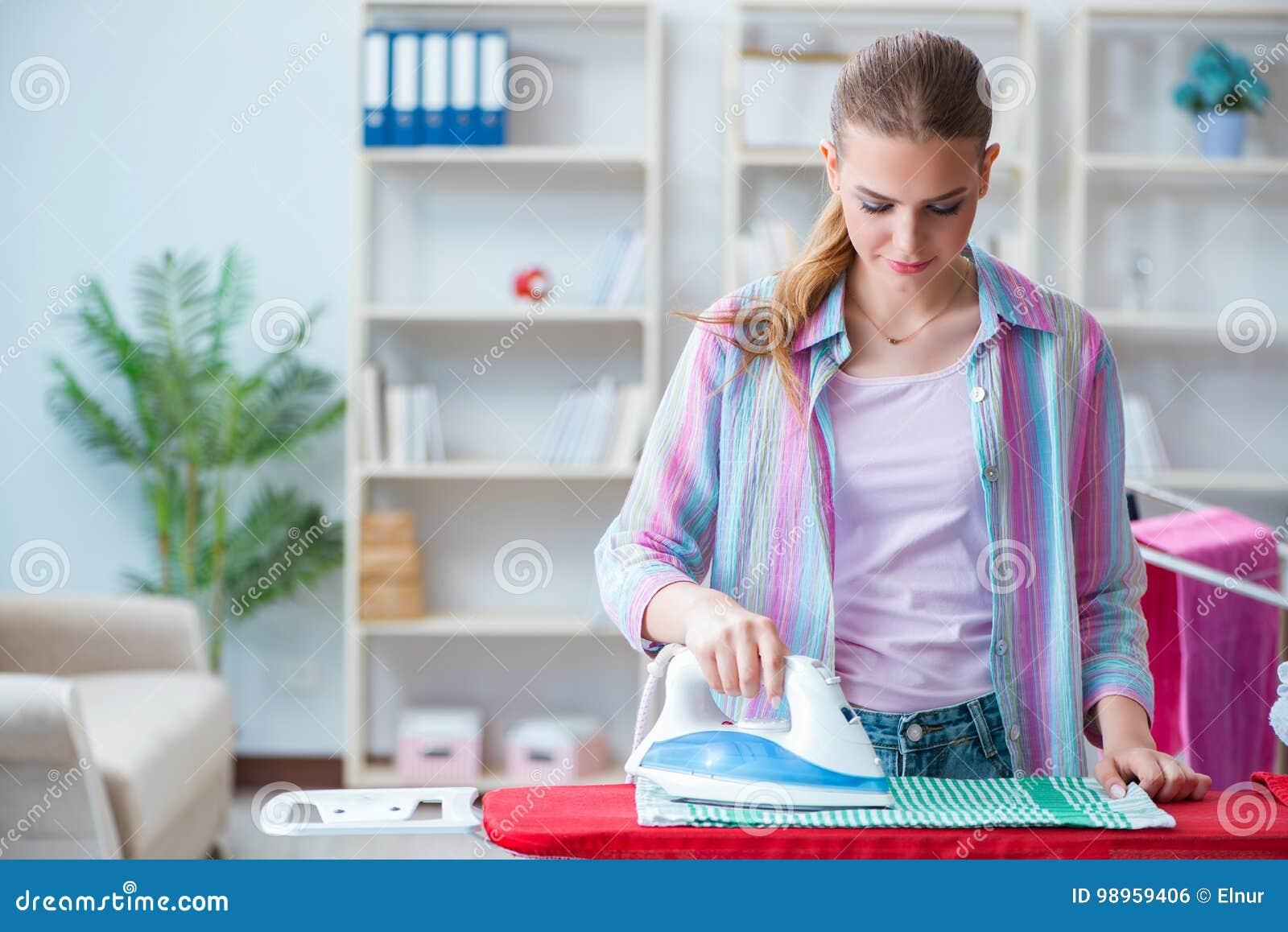 La femme au foyer heureuse faisant repasser à la maison