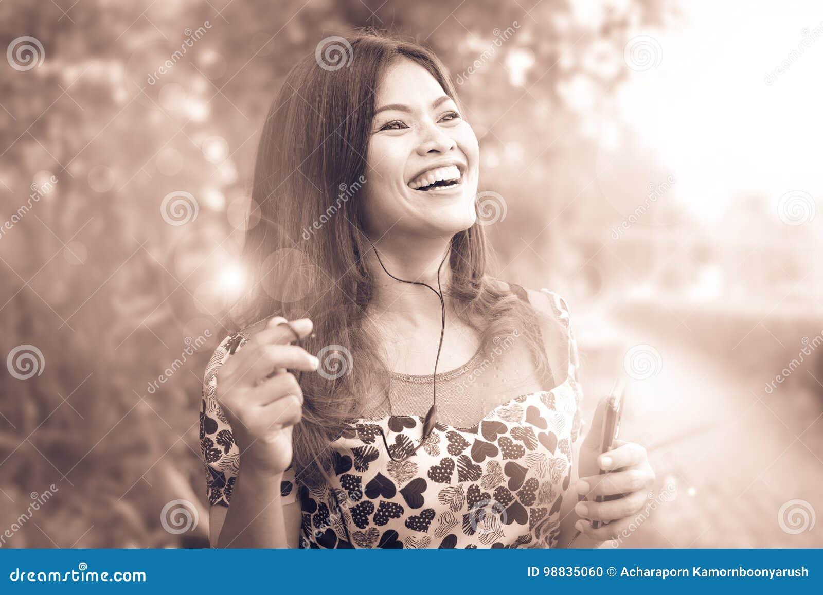 La femme aux cheveux longs écoute heureusement