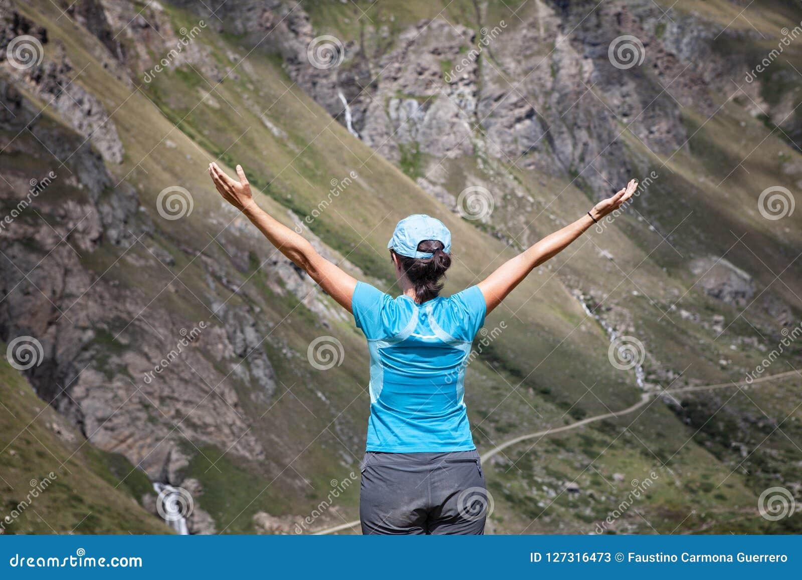 La femme avec des dos ouvrent des bras dans un paysage montagneux