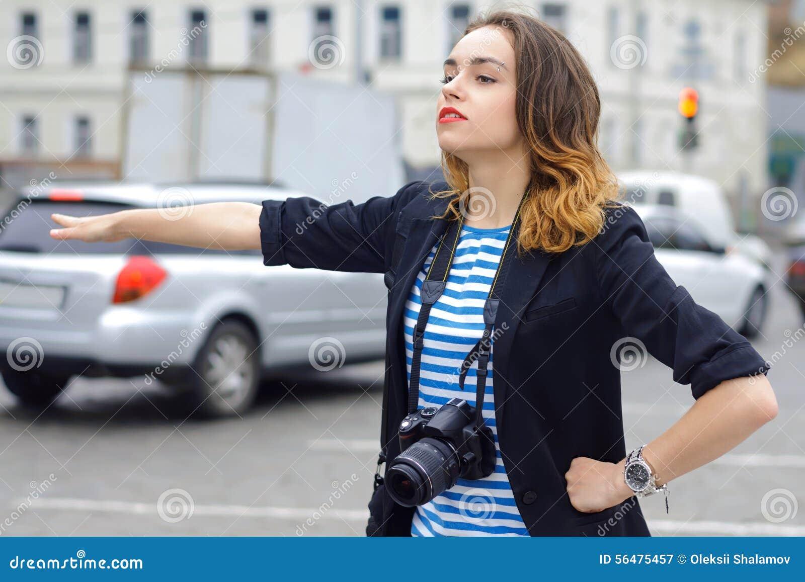 La femme avec l appareil-photo attrape la voiture