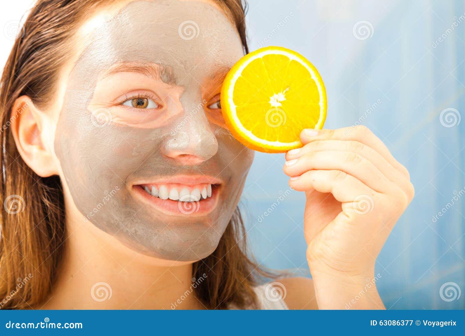 Download La Femme Avec Le Masque Facial De Boue Tient La Tranche Orange Image stock - Image du amusement, argile: 63086377