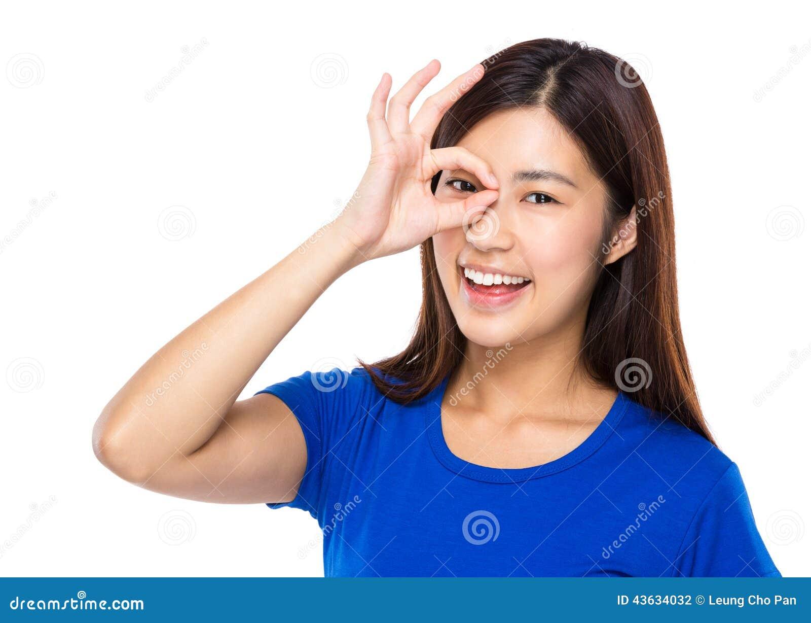 La femme avec le signe correct couvrent son oeil