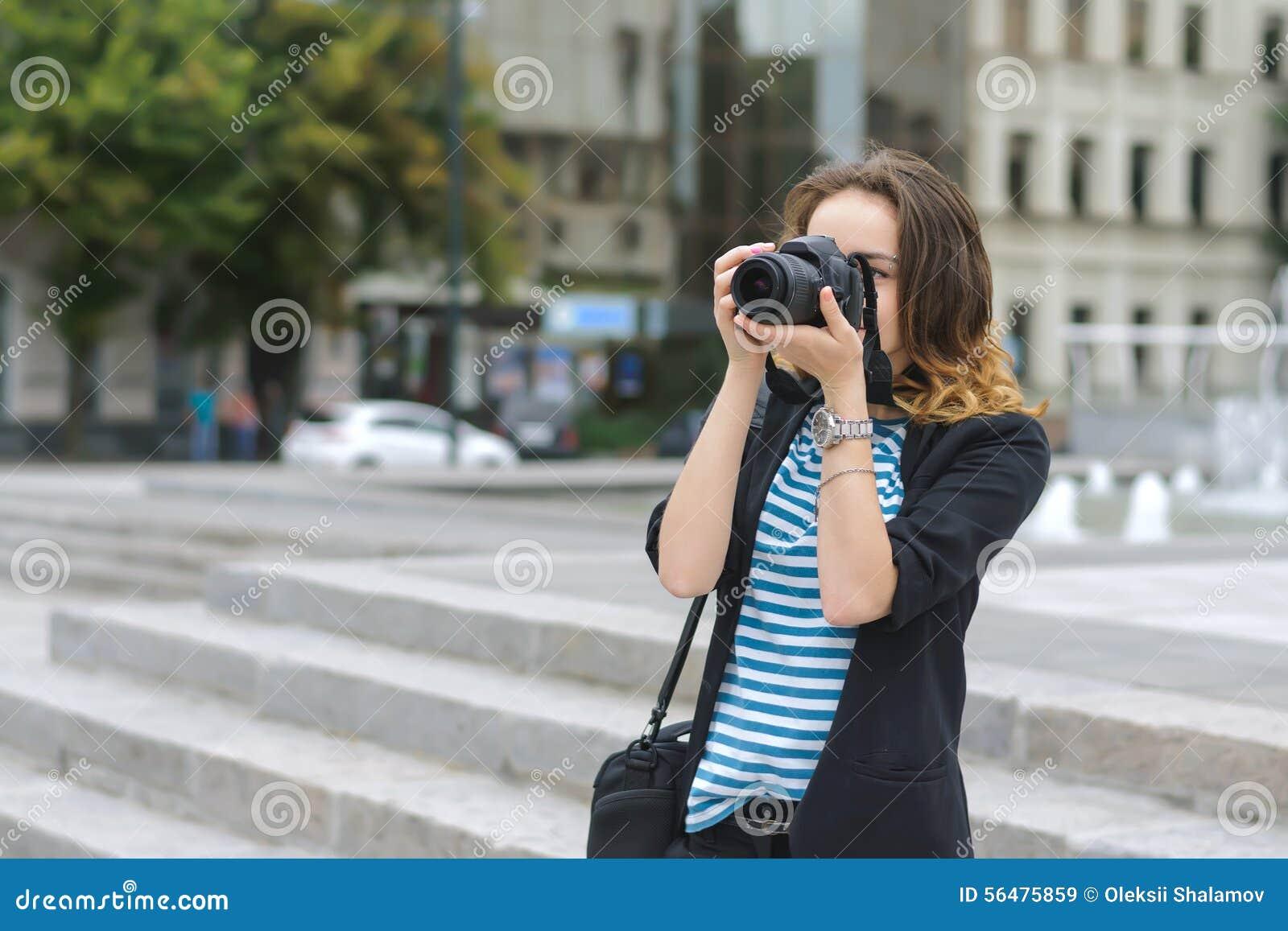La femme avec un appareil-photo photographie la ville