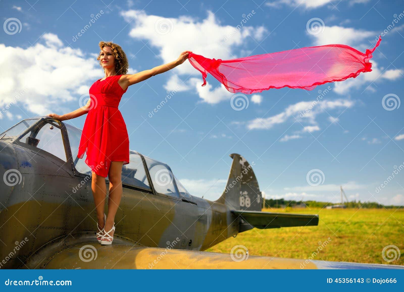 La femme beautyful de mode dans la robe rouge reste sur une aile du vieil avion