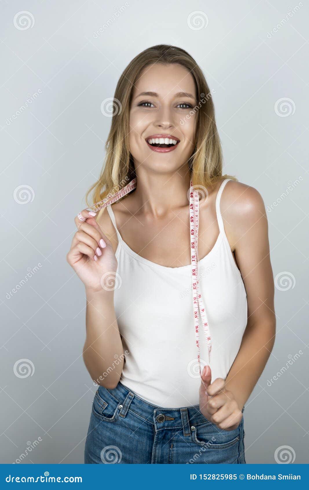 La femme blonde convenable de jeunes semble heureuse tenant le centimètre au-dessus de son fond d isolement blanc de cou