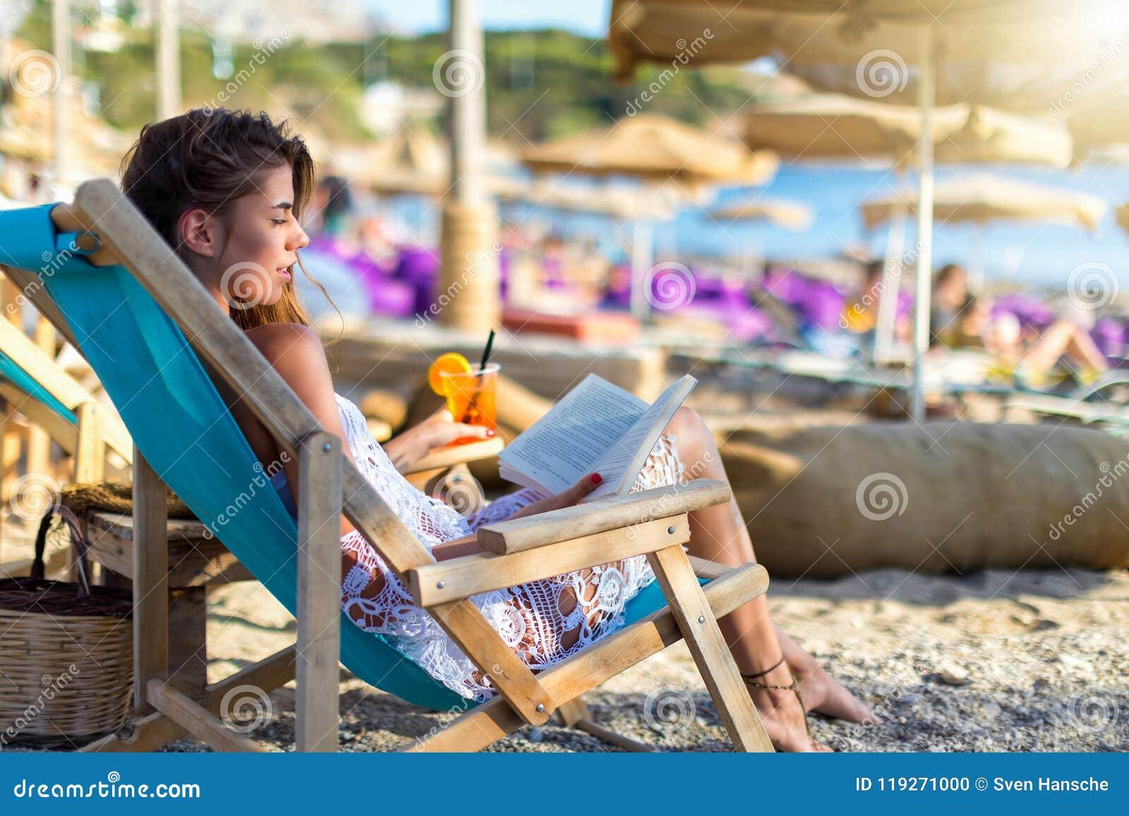 La femme blonde détend dans une chaise du soleil sur une plage