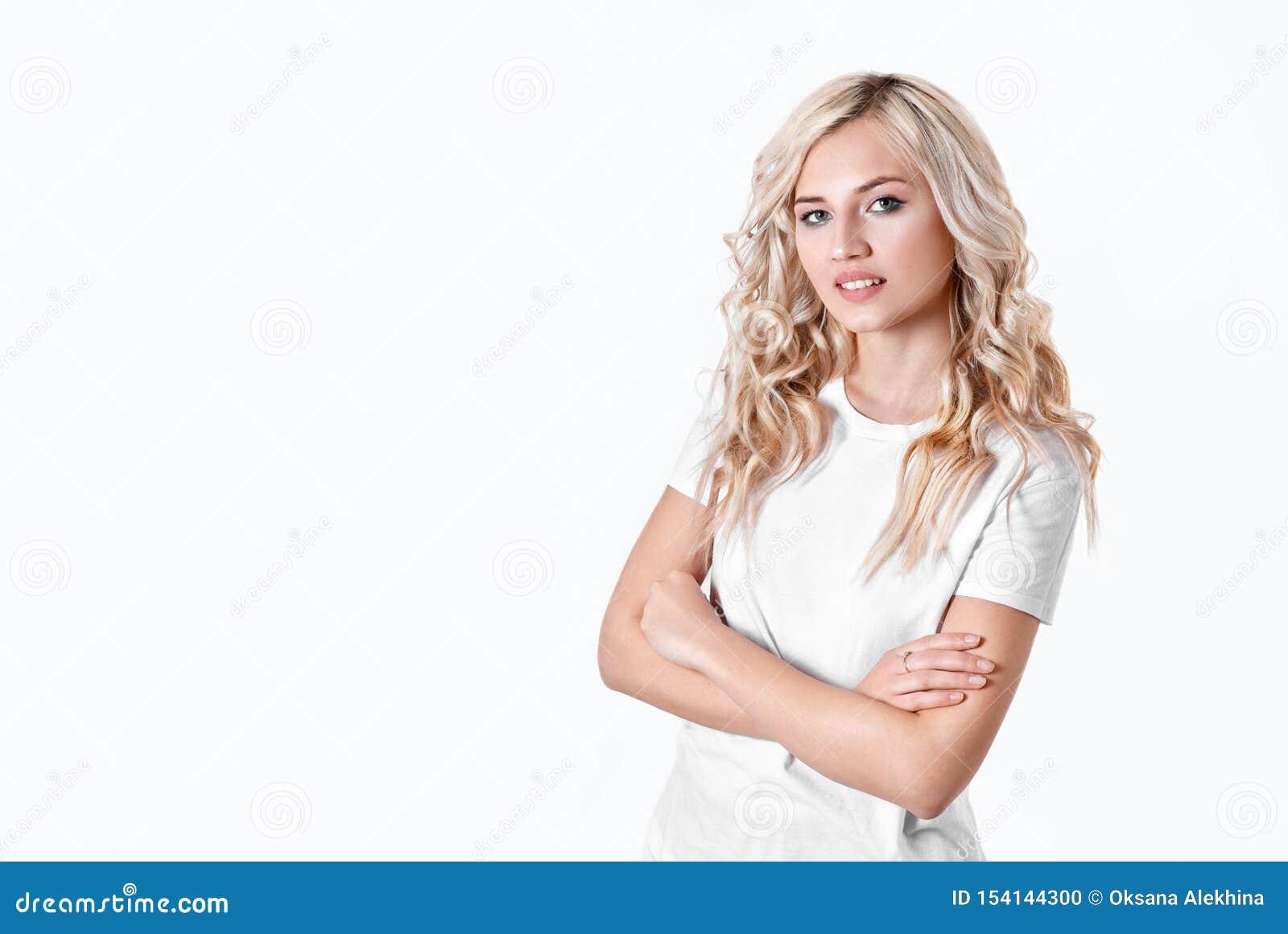 La femme blonde tient un objet imaginaire dans une main sur un fond blanc