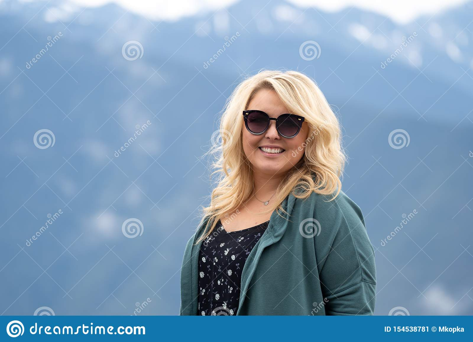 La femme blonde utilisant des lunettes de soleil pose pour un portrait avec les montagnes de cascade à l arrière-plan