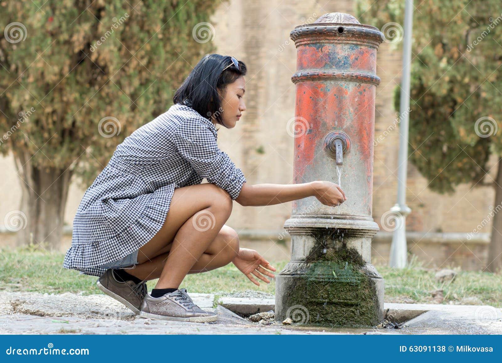 Download La Femme Boit L'eau De L'des Pompes Photo stock - Image du outdoors, public: 63091138