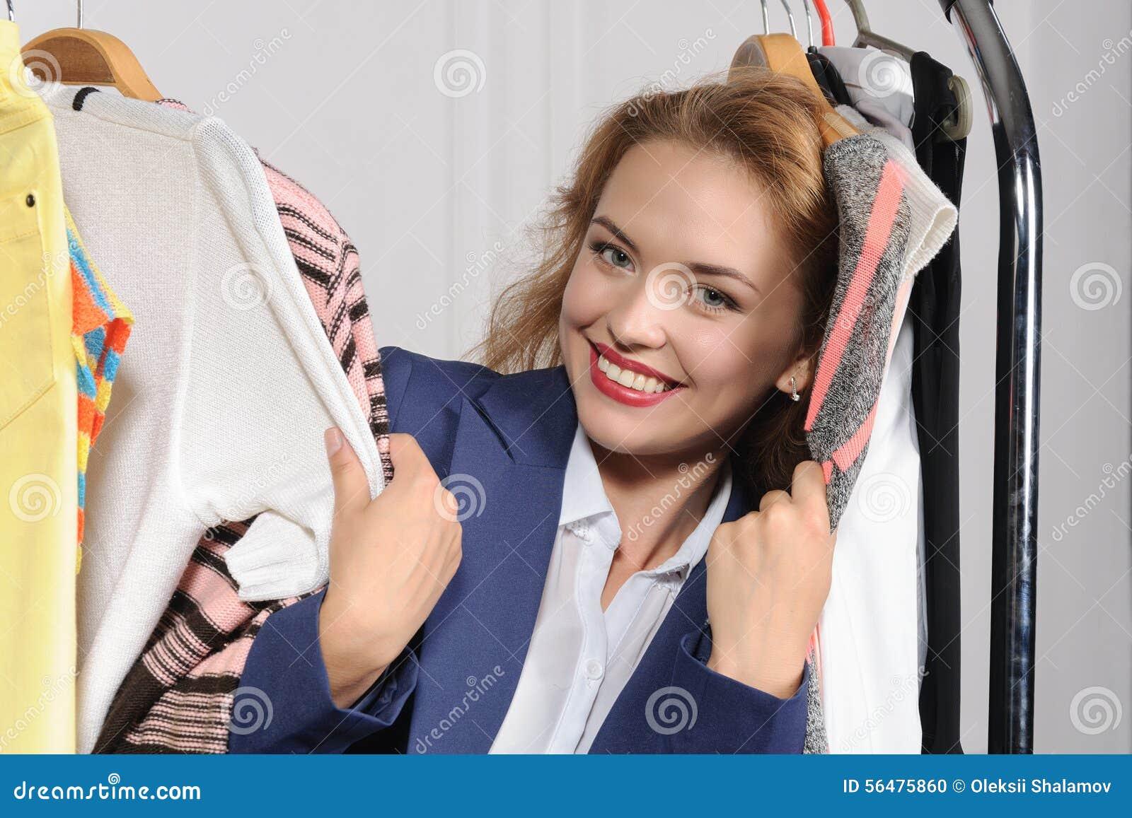 La femme choisit des vêtements dans la boutique de vêtements