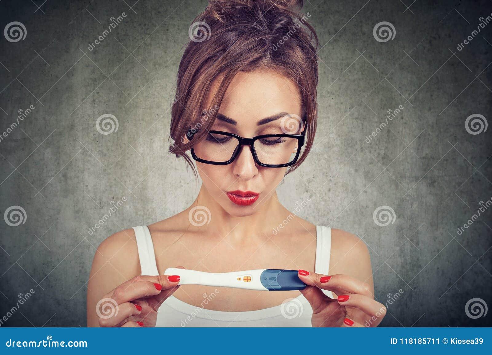 La femme choquée ne peut pas croire ses yeux tout en vérifiant l essai de grossesse positif